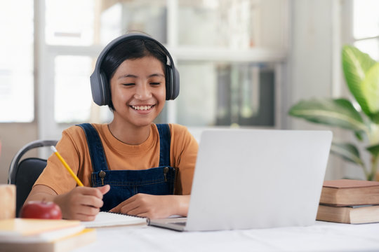 Happy asian girl learning online at home