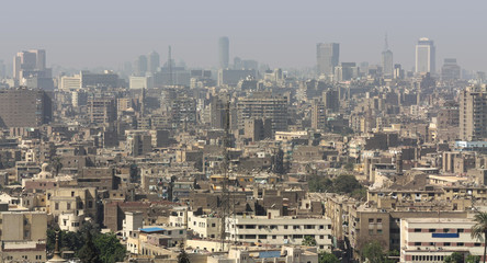 A panoramic view in daylight and sunshine over the big city of Cairo in Egypt. To see with medium-sized buildings and their roofs and in the background many skyscrapers in the haze.