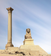 The famous Pompey pillar with a sphinx in the Upper Egyptian city of Alexandria. A popular travel destination. It is day and blue sky. A nice long exposure with moving clouds.