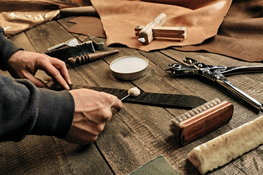 Working process of the leather belt in the leather workshop. Man holding tool. Tanner in old tannery. Wooden table background. Close up man arm. Maintenance concept. Goods production.