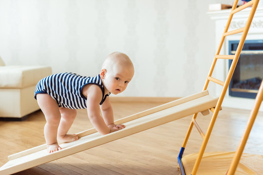 Cute baby performs gymnastic exercises on a wooden home sports complex stairs and rings. Children's sports exercises. Physical education of children at home