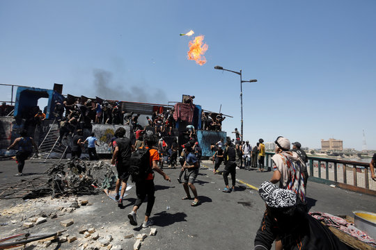 A demonstrator throws a Molotov cocktail during the ongoing anti-government protests after newly-appointed Iraqi Prime Minister Mustafa al-Kadhimi called for the release of all detained protesters, at Jumhuriya bridge in Baghdad