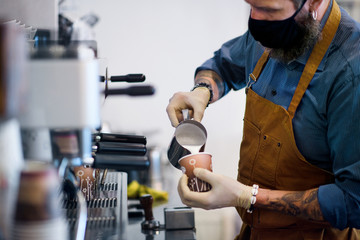 Barista working with gloves, coffee shop open after lockdown quarantine.