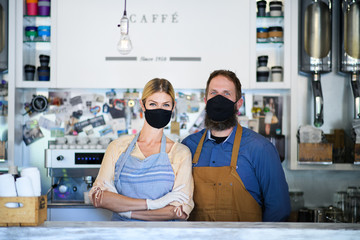 Coffee shop owners with face masks, lockdown, quarantine, coronavirus, back to normal concept.