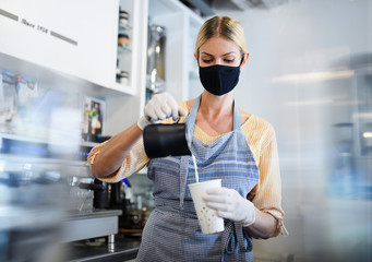 Keuken foto achterwand Hoogte schaal Coffee shop woman owner working with face mask, open after lockdown quarantine.