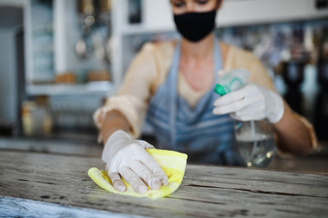 Coffee shop woman owner working with face mask and gloves , disinfecting counter.