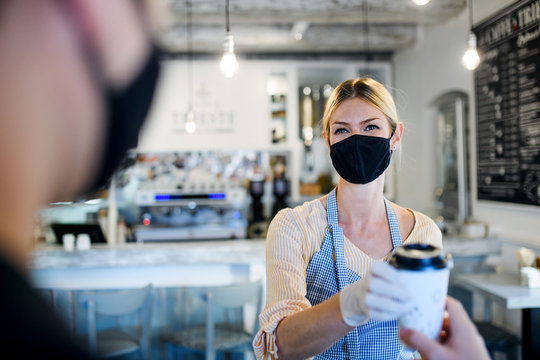 Woman with face mask serving customer, shop open after lockdown quarantine.