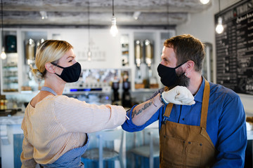 Coffee shop owners with face masks elbow bumping, open after lockdown quarantine.