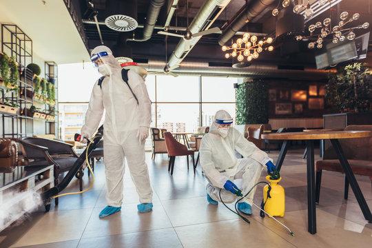 Professional workers in hazmat suits disinfecting indoor of cafe or restaurant, pandemic health risk, coronavirus