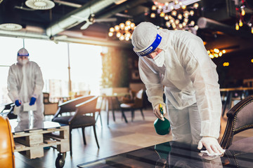 Poster Restaurant Professional workers in hazmat suits disinfecting indoor of cafe or restaurant, pandemic health risk, coronavirus