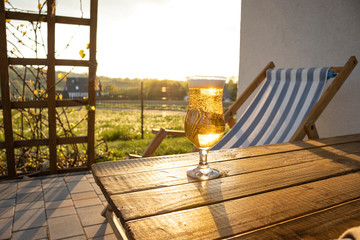 Poster de jardin Bar Glass of beer at the table on patio. Sunset. In background garden and deckchair. Holidays at home.