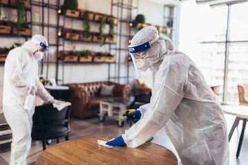 Zelfklevend Fotobehang Restaurant Professional workers in hazmat suits disinfecting indoor of cafe or restaurant, pandemic health risk, coronavirus