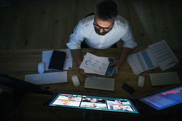 Businessman with computer sitting at desk, working late. Financial crisis concept.