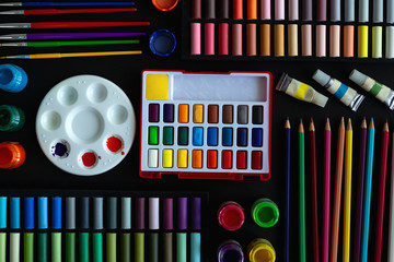 Colorful stationery flat lay: pastel crayons, colored pencils, watercolors on black background. Art...