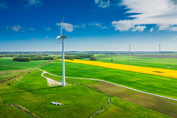 Green fields and wind turbine in spring, aerial view
