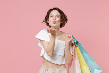 Pretty young woman girl in summer clothes hold package bag with purchases isolated on pink background studio portrait. Shopping discount sale concept. Mock up copy space. Blowing sending air kiss.