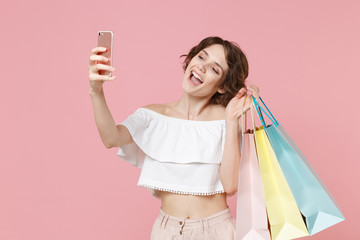 Funny young woman girl in summer clothes hold package bag with purchases isolated on pink background in studio. Shopping discount sale concept. Mock up copy space. Doing selfie shot on mobile phone.