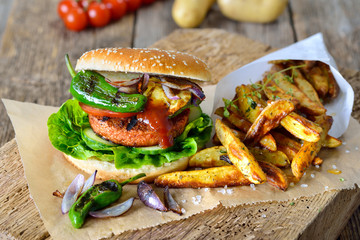 Veganer Burger mit Soja-Seitan-Patty und Grillgemüse mit Pimientos dazu knusprige Pommes – Meatless street food – delicious veggie burger with soy patty and grilled vegetable served with potato wedges