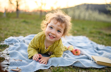 Small toddler girl outdoors on blanket in spring, looking at camera.
