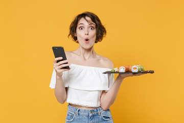 Young woman girl in casual clothes hold in hand makizushi sushi roll served on black plate japanese food using mobile cell phone isolated on yellow background studio portrait. People lifestyle concept