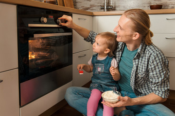Father and kid waiting for freshly baked buns near oven