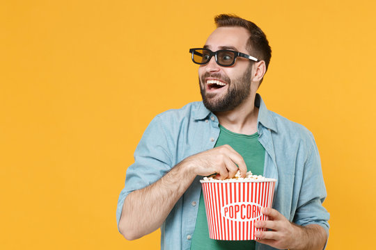Excited young man in casual clothes 3d glasses isolated on yellow background in studio. People sincere emotions in cinema, lifestyle concept. Watching movie film hold bucket of popcorn looking aside.
