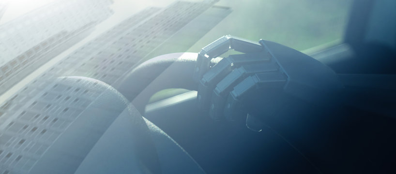 Robot arm on a steering wheel. Artificial intelligence drives a car. Autonomous vehicle concept.