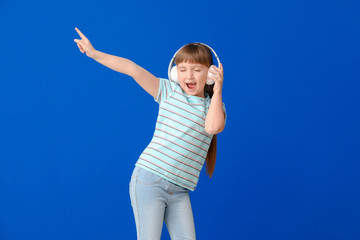 Cute little girl dancing and listening to music against color background