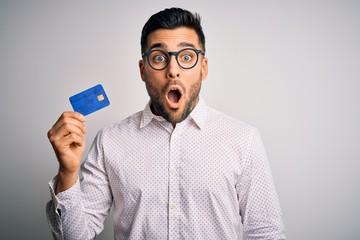 Young business man holding credit card over isolated background scared in shock with a surprise face, afraid and excited with fear expression