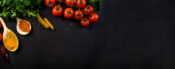 Food background with colorful food ingredients border from above. Top view of parsley, cherry tomato, herbs and spices on rustic black table.