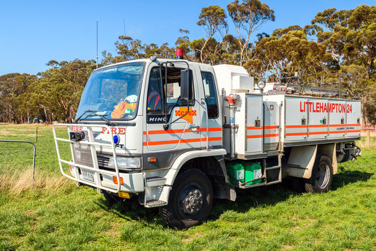 Adelaide Hills, South Australia - February 9, 2020: South Australian Country Fire Service truck parked on the green grass on a bright warm summer day