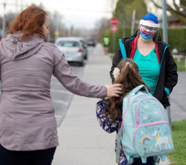 A teacher greets a student and her mother as schools reopen outside the greater Montreal region in Saint-Jean-sur-Richelieu