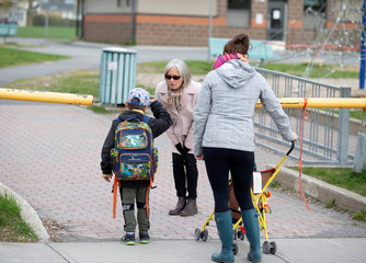 A student is greeted by a teacher as schools reopen outside the greater Montreal region in Saint-Jean-sur-Richelieu