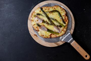 selbstgemachte Pizza mit Mascarpone, Mozzarella, Sauce hollandaise, grünem Spargel, Truthanschinken auf einer Seite, Studio
