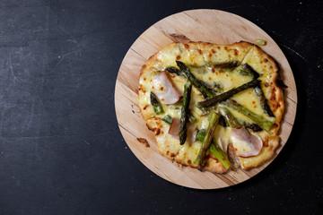selbstgemachte Pizza mit Mascarpone, Mozzarella, Sauce hollandaise, grünem Spargel, Truthanschinken auf einer Seite, geschnitten, Studio