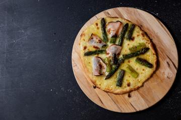 selbstgemachte Pizza mit Sauce Hollandaise, Mozzarella, grüner Spargel und Truthanschinken, Studio