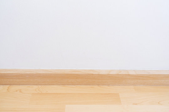 Wooden wall base skirting, finishing material with wood laminate floor and white mortar wall.