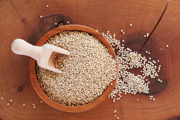Quinoa seeds in wooden bowl and scoop on wooden board (Chenopodium quinoa)