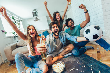 Very excited friends having fun by watching football match and eating at home, indoors. Friendship, leasure, rest, home party concept