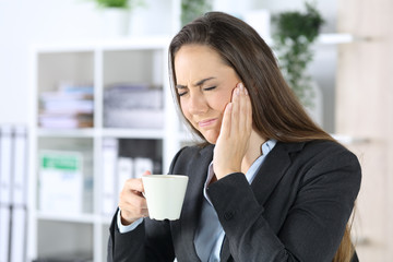 Executive with toothache holding coffee at office