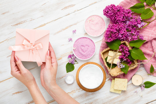 Present box in female hands. Spa and bath cosmetics with lilac flowers. Bath salt, soap, cream, oil, serum and towel rolls. Organic natural cosmetics. Beauty and relax healthcare. Gift certificate