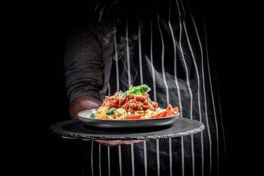 Man holding plate of delicious Italian spaghetti pasta on a dark background
