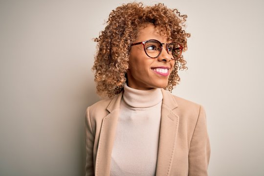 Beautiful african american businesswoman wearing glasses over isolated white background looking away to side with smile on face, natural expression. Laughing confident.