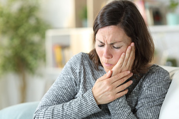 Middle age woman suffering toothache at home