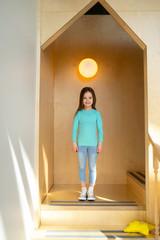 Adorable little girl standing in children playroom