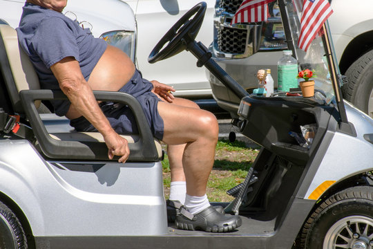 Overweight and out of shape, a senior man with a beer belly smokes a cigarette while riding a golf cart.