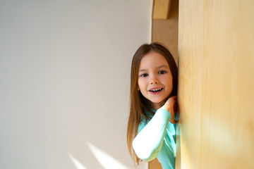 Cute little girl peeking out from behind the wall