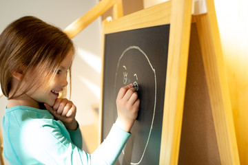 Smiling little girl drawing face on chalkboard