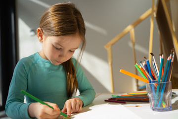 Cute little girl drawing on piece of paper at home