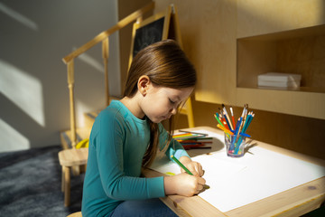 Adorable little girl drawing on piece of paper at home